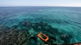 FILE - Philippine Marine, right, swims in the waters of Second Thomas Shoal in the South China Sea.