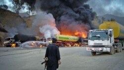 یک نیروی امنیتی در نزدیکی یک تانکر سوخت برای نیروهای ناتو که در نزدیکی گذرگاه مرزی طورخم در آتش می سوزد - ۷ ژوئن ۲۰۱۱