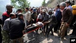Para penambang dan tim SAR membawa seorang penambang yang terluka akibat ledakan di tambang batu bara dekat Azadshahr di Iran utara, 3 Mei 2017. (AP Photo/Tasnim News Agency, Mostafa Hassanzadeh)