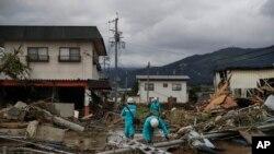 Pekerja menyurvei kerusakan di lingkungan yang hancur akibat Topan Hagibis Selasa, 15 Oktober 2019, di Nagano, Jepang. (Foto: AP / Jae C. Hong)