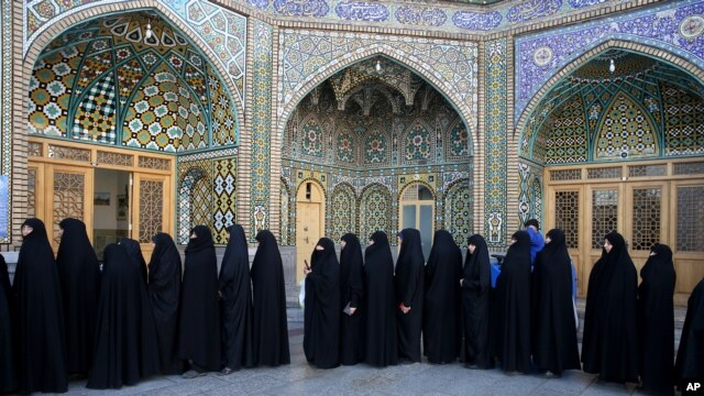Iranian women stand in line at a polling station during the parliamentary and Experts Assembly elections in Qom, 125 kilometers (78 miles) south of the capital Tehran, Iran, Friday, Feb. 26, 2016. (AP Photo/Ebrahim Noroozi)