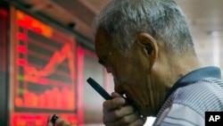 9일 중국 베이징의 증권거래소에서 한 투자가가 돋보기를 들고 증시를 살피고 있다.