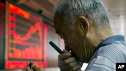 一中国股民7月9日在北京一家交易厅用放大镜查看手机上的股市价格。