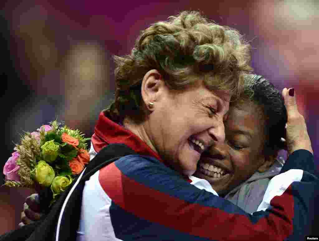 Gabrielle Douglas, de Estados Unidos, recibe un abrazo de una entrenadora luego de ganar la medalla de oro en gimnasia artística femenina individual.