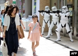 "Pedestrians pass before Storm Troopers at a toy shop in Tokyo. May 4th is called the ""Star Wars Day"" among Star Wars fans as the famous phrase ""May the Force be with you"" in the movie sounds like ""May the 4th be with you,"" May 4, 2015."