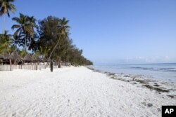 A villager walks along a deserted beach near a seaside resort on the East African archipelago of Zanzibar, Oct. 12, 2010.