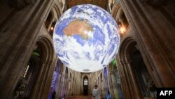 A member of the clergy poses under British artist Luke Jerram's installation 'Gaia', a 7 meter replica of planet Earth, suspended in the nave of Ely Cathedral in Ely, Cambridgeshire, on June 30, 2021.