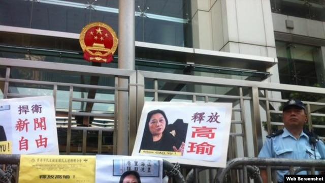 示威者在香港中联办大楼外面放置了要求释放高瑜的标语和图片,旁边是警察(2015年4月17日,网络资料图片)