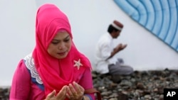 Một phụ nữ cầu nguyện nơi ngôi mộ tập thể các nạn nhân sóng thần ở Aceh Besar, Indonesia, 26/12/14