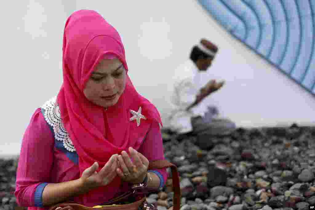A woman mourns victims of the December 2004 Asian tsunami, praying at a mass grave in Siron, Aceh Besar, Indonesia, Dec. 26, 2014.