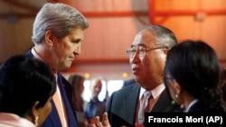 时任美国国务卿克里和中国气候特使解振华在联合国气候变化框架公约签约国第21次会议上交谈。(2015年12月12日)
