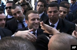 FILE - French President Emmanuel Macron shakes hands as he meets residents in Algiers, Algeria, Dec.6, 2017.
