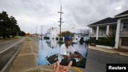 Fotografer Carlos Barria menunjukkan gambar yang diambilnya pada tahun 2005, dan mencocokkannya dengan kondisi saat ini di lokasi yang sama di New Orleans, 16 Agustus 2015 (Foto: dok).