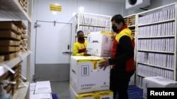 Karyawan di fasilitas penyimpanan dengan lemari dingin di pusat distribusi pos dan logistik Jerman, Deutsche Post DHL di Gurugram, India, 26 November 2020. (REUTERS / Anushree Fadnavis)