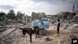 Một bé trai Palestine đứng bên cạnh chiếc xe lừa chở đồ từ ngôi nhà bị phá hủy của gia đình cậu bé ở thị trấn Beit Lahiya, phía bắc Dải Gaza, ngày 11/8/2014.
