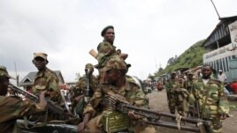 Congolese rebels sit in a truck as they patrol a street in Sake, 25 kilometers north of Goma city soon after the rebels captured the town from the government army, in the eastern Democratic Republic of Congo, November 21, 2012.