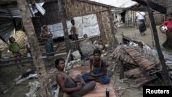 FILE - Rohingya people pass their time in a damaged shelter in Rohingya IDP camp outside Sittwe, Rakhine state, Aug. 4, 2015. Kerry noted the Rohingya as a group that has been 'singled out' for discrimination.