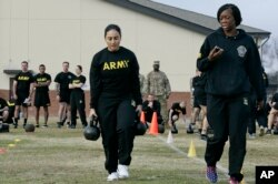 U.S. Army Staff Sgt. Idis Arroyo,left, carries weights while training to serve as an instructor in the new Army combat fitness test at Fort Bragg, N.C., Jan. 8, 2019.