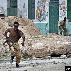 A government soldier runs for cover during heavy clashes in northern Mogadishu between Somali government troops and insurgent forces (File)
