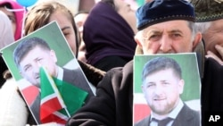 FILE - People hold portraits of Chechen leader Ramzan Kadyrov as they take part in a rally marking the 13th anniversary of the adoption of the Constitution of Russian region of Chechnya, in the regional capital of Grozny, March 23, 2016.