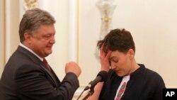 Ukrainian President Petro Poroshenko, left, looks at newly-released Ukrainian pilot Nadiya Savchenko during their meting in the Presidential Office in Kyiv, Ukraine, May 25, 2016.
