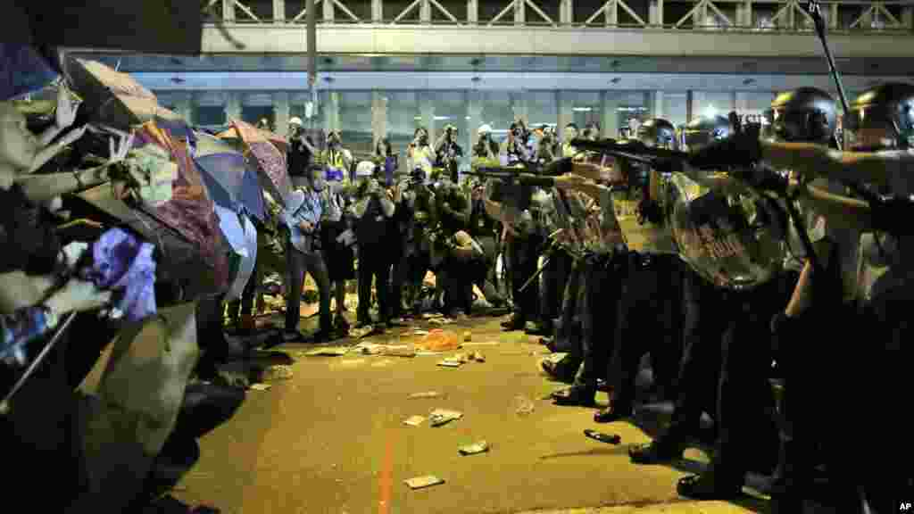 Riot police officers try to stop protesters from moving forward on a pro-democracy protest encampment in the Mong Kok district of Hong Kong early, Oct. 19, 2014.