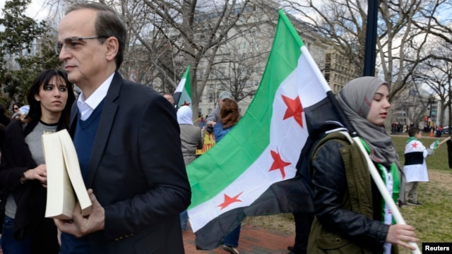 Chief Syrian Opposition Coalition negotiator Hadi al-Bahra (L) awaits his turn to address dozens of protestors gathered to mark the third anniversary of the Syrian revolution, in Lafayette Park, across from the White House in Washington, March 15, 2014.