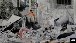加沙地帶的巴勒斯坦人星期六檢視遭以色列空襲後的建築。