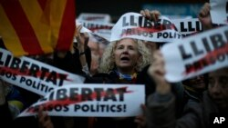 """Demonstrators gather during a protest calling for the release of Catalan jailed politicians, in Barcelona, Spain, Nov. 11, 2017. Eight members of the now-defunct Catalan government remain jailed in an alleged rebellion case. The banners read in Catalan: """"Freedom for the political prisoners."""""""