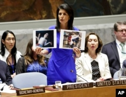 Nikki Haley, United States' Ambassador United Nations, shows pictures of Syrian victims of chemical attacks as she addresses a meeting of the Security Council on Syria at U.N. headquarters in New York, April 5, 2017.