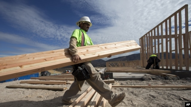 Construction worker Miguel Fonseca carries lumber as he works on a house frame for a new home, Chula Vista, Calif., Nov. 16, 2012.