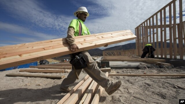 Construction worker Miguel Fonseca carries lumber as he works on a house frame for a new home, Nov. 16, 2012, in Chula Vista, California.