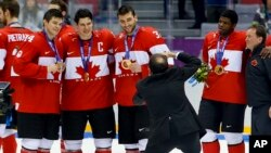 Some members of the Canadian ice hockey team pose for a photo after beating Sweden 3-0 in the men's gold medal ice hockey game at the 2014 Winter Olympics, Sunday, Feb. 23, 2014, in Sochi, Russia.