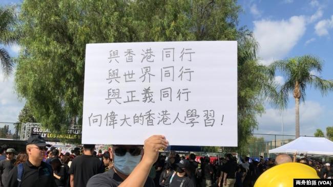 """""""全球反独裁集会""""洛杉矶巴恩斯公园力挺香港活动中,一名自称移居中华民国的男子举牌支持香港"""