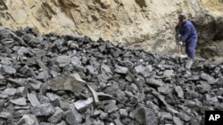 A worker shovels coal at coal mine owned by Puda Coal Inc. in Pinglu, Shanxi province. Puda Coal Inc, an independent coking coal producer in northern China's Shanxi province, (File)