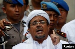 FILE - Habib Rizieq gestures while speaking to the media upon his arrival at Jakarta Police headquarters in Jakarta, Indonesia, Feb. 1, 2017.