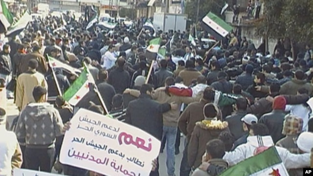 Demonstrators protest against Syria's President Bashar al-Assad after Friday prayers, with banners that read, 'Yes to support the Free Army,' in Al Qusour, Homs, Syria, March 2, 2012.