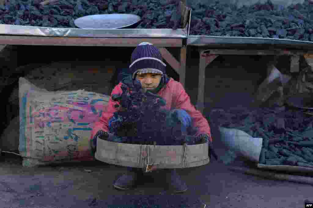 A young Afghan vendor sifts charcoal at his stall in Herat city.