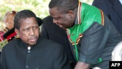 Then-acting President Edgar Lungu (l) talks to foreign affairs minister Harry Kalaba during a military exhibition march, Oct. 24, 2014 to mark Zambia's 50th Independence celebration.