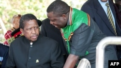 FILE - Then-acting President Edgar Lungu (l) talks to foreign affairs minister Harry Kalaba during a military exhibition march, Oct. 24, 2014 to mark Zambia's 50th Independence celebration.