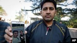 پاکستانی تاجر عمران بیگ اپنی لاپتہ ویغور چینی بیوی کی تصویر دکھا رہا ہے۔ فائل فوٹو