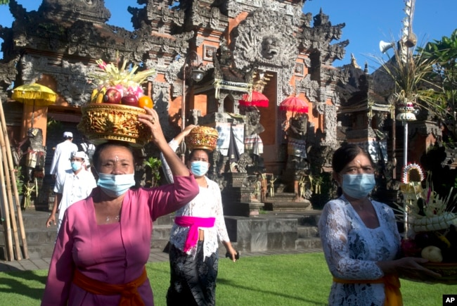 Orang-orang yang memakai masker sebagai tindakan pencegahan penyebaran virus corona membawa sesaji selama festival Hindu Galungan, di sebuah pura di Bali, pada Rabu, 14 April 2021. (Foto: AP)
