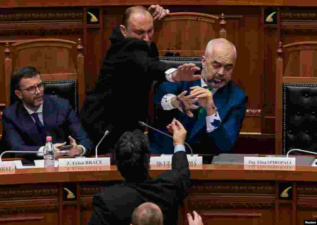 Albania Prime Minister Edi Rama reacts as ink is thrown at him by members of the opposition during a parliamentary session in Tirana.