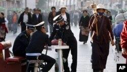 Petugas keamanan mengamati peziarag Budha saat berjalan di Barkhor, sekitar kuil Jokhang di Lhasa, ibukota Tibet, Tiongkok (Foto: dok). Tiongkok terus berupaya untuk menghentikan aksi bakar diri warga Tibet.