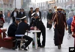 2009年6月19日保安人员在西藏首府拉萨观察走在八廓街上的佛教朝圣者