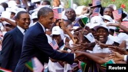 U.S. President Barack Obama and Tanzania's President Jakaya Kikwete (L) greet Tanzanians during an official welcoming ceremony in Dar Es Salaam July 1, 2013.