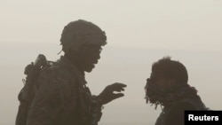在阿富汗东部楠格哈尔省一个美军和阿富汗警方的检查哨所,一名美国士兵和一名翻译对话的侧影(资料图片)