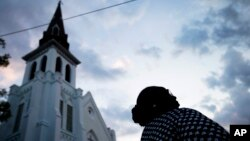 FILE - A woman stands next to Emanuel AME Church, the site of the mass shooting, as the sun rises, June 26, 2015, in Charleston.
