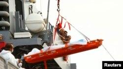 Pelaut Malta menyaksikan pengangkatan jenazah migran yang tenggelam. (Reuters) /Darrin Zammit Lupi
