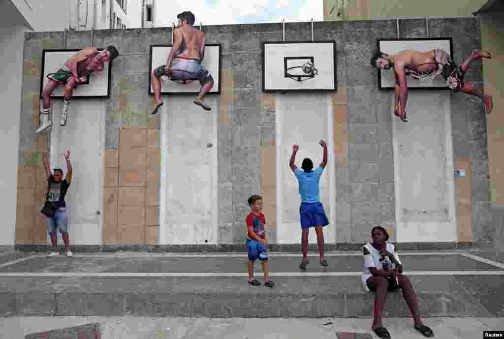 កុមារលេងបាល់បោះនៅកន្លែងមួយដែលសិល្បករជនជាតិអេស្ប៉ាញ Martin និង Sicilia បានតម្លើងនៅក្នុងកម្មវិធីតាំងពិព័រណ៌សា្នដៃសិល្បៈ Havana Biennial លើកទី១៣ ក្នុងទីក្រុង Havana ប្រទេសគុយបា។